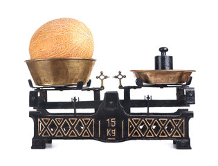 Old-fashioned balance scale with melon