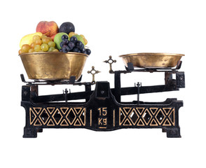 Old-fashioned balance scale with fruits
