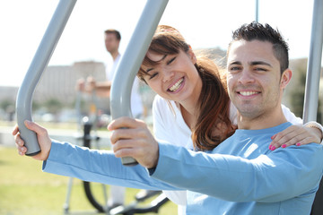Smiling woman and man using fitness machines