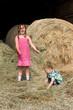 Kinder spielen im Heu