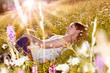 Mädchen liegt in Blumenwiese im Sonnenuntergang / marguerite-la