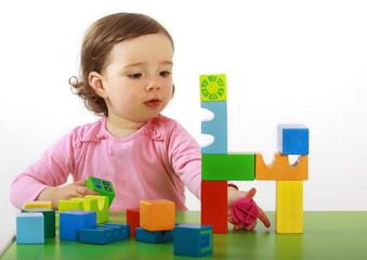 Ein Kleinkind baut eine Brücke aus Holzbausteinen