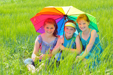 kids with umbrella  on field