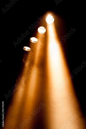 Four spotlights with orange beams