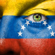 Flag painted on face with green eye to show venezuela support
