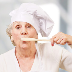 portrait of cook senior woman with wooden spoon on mouth indoor