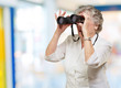 portrait of senior woman looking through a binoculars indoor