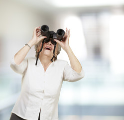 portrait of senior woman looking through a binoculars, indoor
