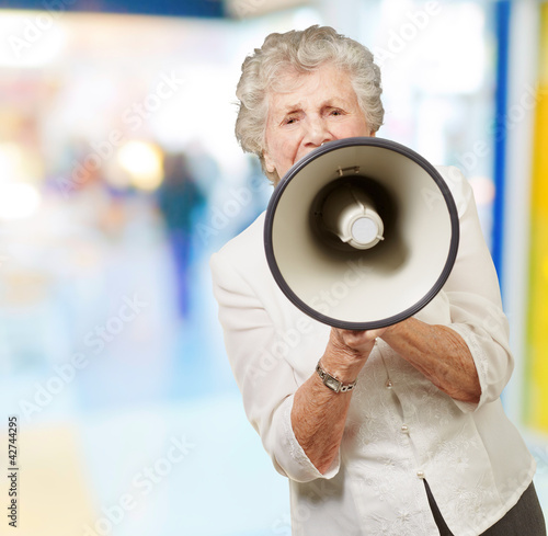 portrait of senior woman screaming with megaphone at crowded pla
