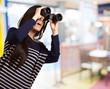portrait of young girl looking through a binoculars indoor