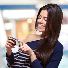 portrait of young woman touching a modern mobile indoor
