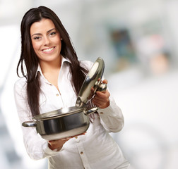 portrait of young girl opening sauce pan indoor