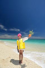 波打ち際でパイナップルを持っている笑顔の女の子