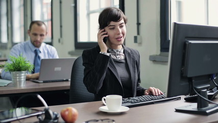 Businesswoman talking on cellphone in front of the computer