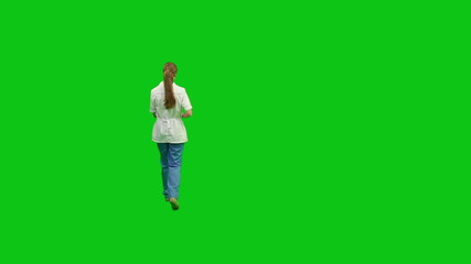 Young nurse moves around with a report. Green screen.