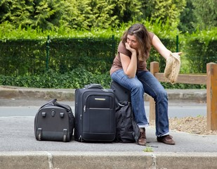 auto stoppeuse assise sur ses baggages, découragement complet !