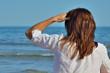 Jeune femme qui regarde au loin vers le large