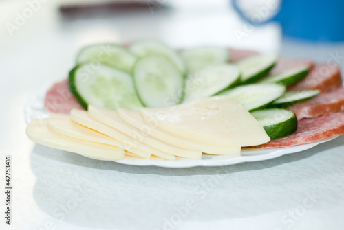 Dish with cut sausage, cheese and a cucumber