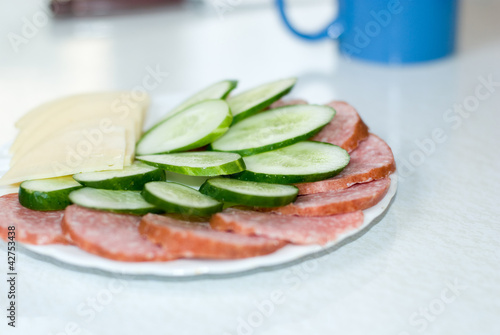 Cut cheese, sausage and cucumber in a plate