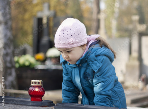 Girl mourning at the grave on cemetery in Warsaw