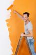 mann streicht eine wand orange