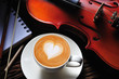 Latte art and violin on wooden table