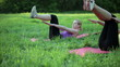 Two women doing sit ups in a park, tracking shot
