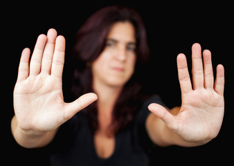 Woman with her two hands signaling to stop on a black background