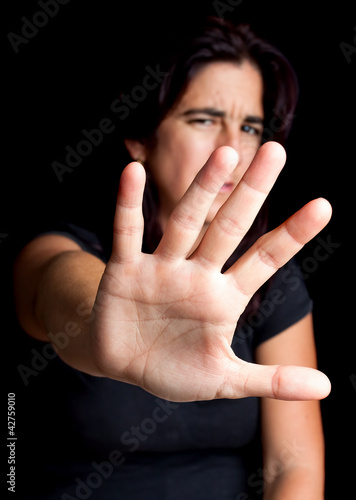 Frightened woman with her hand extended for protection