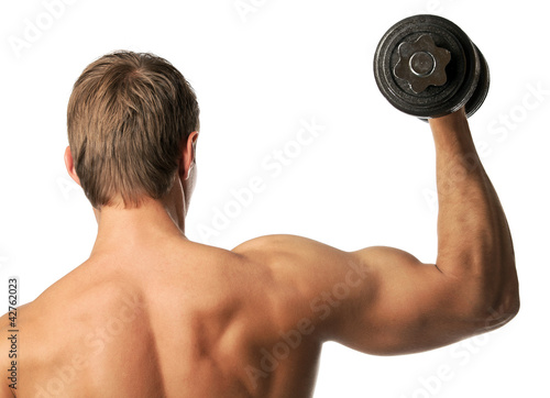 Muscular young man lifting a dumbbell, rear view