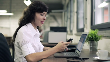 Young businesswoman with smartphone and laptop in the office