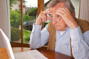 Senior sitzt genervt vor dem Laptop