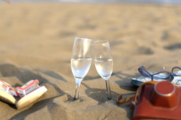 Two glasses, slippers and old camera in the sand