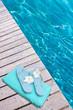 serviette et tongs sur margelle de piscine