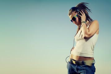 girl with headphones against the sky