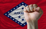 us state flag of arkansas with hard fist in front of it symboliz