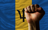 Hard fist in front of barbados flag symbolizing power