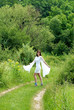 woman in white dress on green rural road