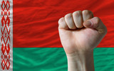 Hard fist in front of belarus flag symbolizing power