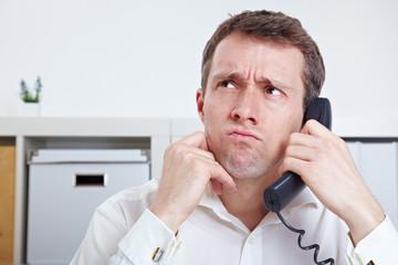 Frustierter Geschäftsmann am Telefon