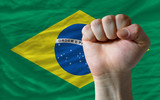 Hard fist in front of brazil flag symbolizing power