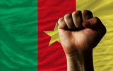 Hard fist in front of cameroon flag symbolizing power
