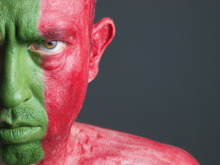 Man with his face painted with the flag of Portugal