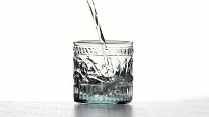 Eau remplissant un verre qui déborde au ralenti