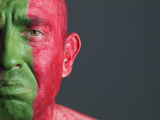 Man face painted flag of Portugal, sad expression.