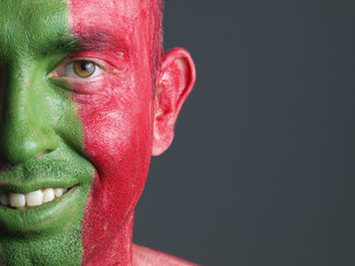 Man smiling and his face painted with the flag of Portugal.
