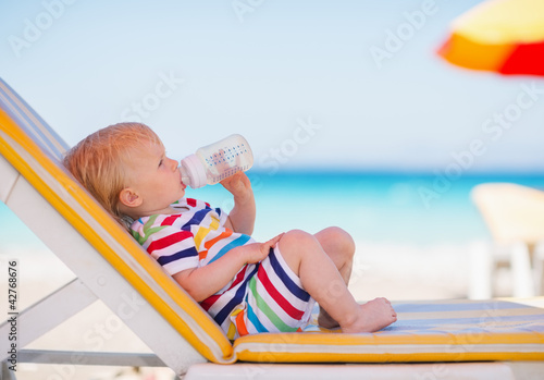 Portrait of baby on sunbed drinking water - 42768676