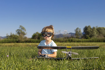 Cute young boy and his RC plane, sitting on grass