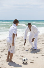 African American Father & Son Playing Football Soccer on Beach