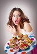 young surprised woman eating cakes isolated on white